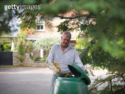 Man putting kitchen waste into compost bin - gettyimageskorea