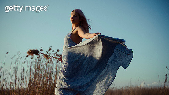 Young Woman In Long dress dancing on the field - gettyimageskorea