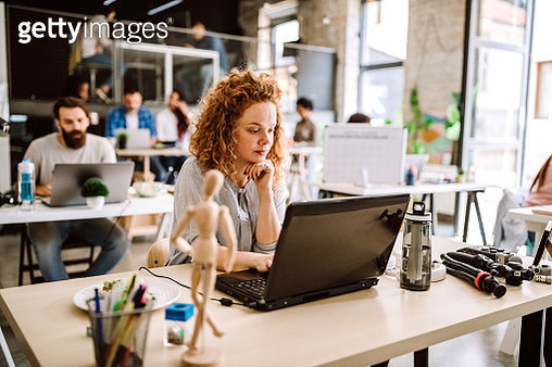 Happy young redhead woman working cheerfully at comfortable office - gettyimageskorea
