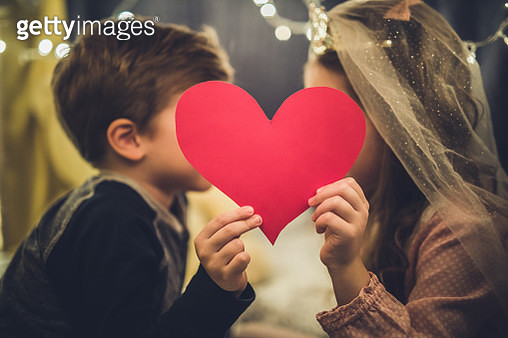 Close up of romantic kids holding red heart inside of a tent. - gettyimageskorea