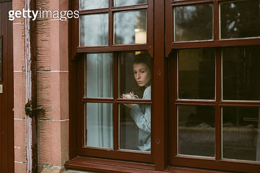 Young woman looking out of the window in a brick house in Scotland with a cup of tea during Coronavirus pandemic Covid-19 - gettyimageskorea