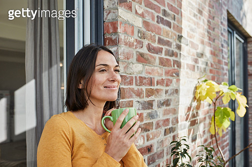 Smiling woman drinking from cup in front of her home - gettyimageskorea
