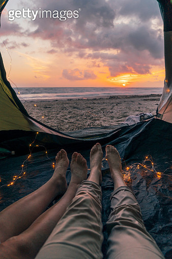 Young adult couple sleeping in a tent on the beach - gettyimageskorea