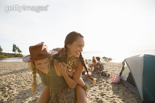 Woman piggybacking friend on beach - gettyimageskorea