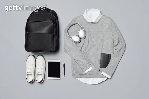 Overhead view of backpack with shoes and technologies. Flat lay of travelers clothing and personal accessories. Menswear is arranged on gray background. - gettyimageskorea