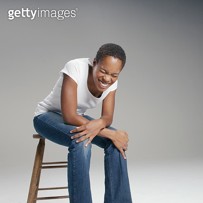 Young woman sitting on stool and laughing - gettyimageskorea