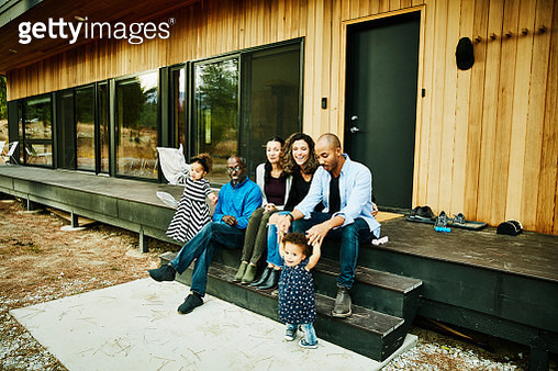 Smiling multigenerational family hanging out together on porch of cabin - gettyimageskorea