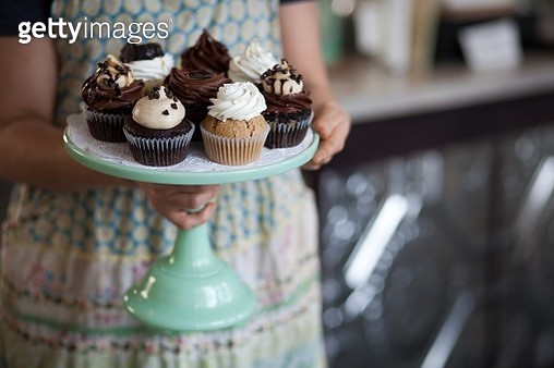 Bakery owner carrying tray of allergy-friendly cupcakes - gettyimageskorea