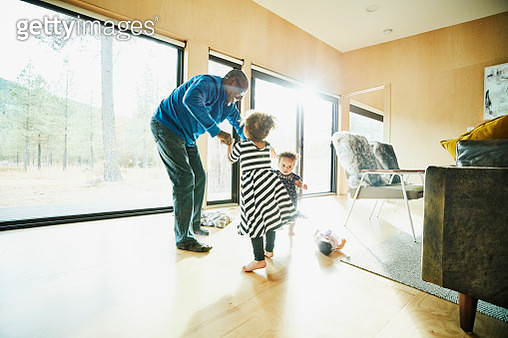 Smiling grandfather dancing with two granddaughters in living room - gettyimageskorea