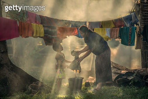A mother and child washing clothes in Thailand. - gettyimageskorea