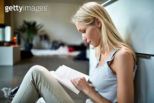 Young woman sitting on floor at home reading book - gettyimageskorea