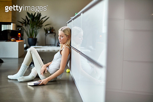 Young woman sitting on floor at home with book - gettyimageskorea