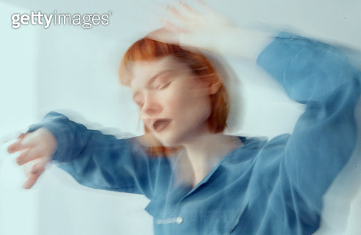 Red haired woman in blue shirt dancing, blurred motion - long exposure - gettyimageskorea
