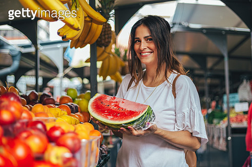 A young woman holding a watermelon at the market - gettyimageskorea