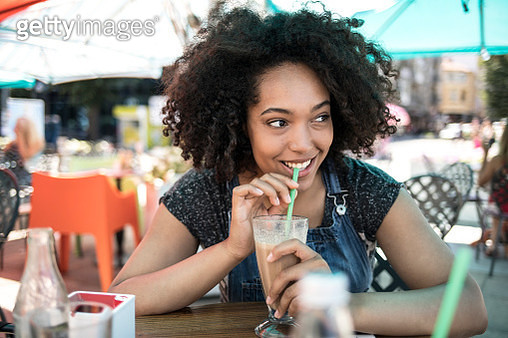 Smiling african woman drinking cocktail in cafeteria - gettyimageskorea