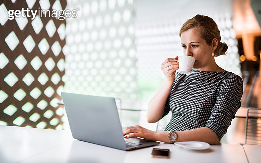 Blondie businesswoman drinking coffee and typing on laptop in office. - gettyimageskorea