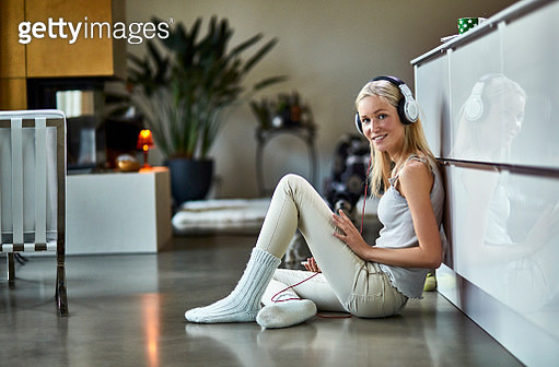 Portrait of young woman wearing headphones listening to music at home - gettyimageskorea