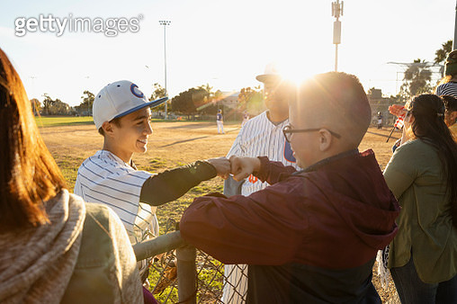 Baseball player fist bumping friend at sunny fence - gettyimageskorea