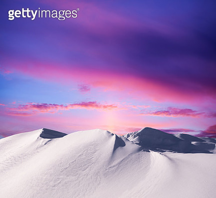 Snowcapped mountains at sunset. - gettyimageskorea