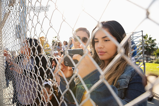 Latinx young woman using smart phone behind fence at baseball game - gettyimageskorea