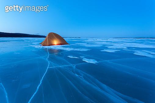 Russia, Amur Oblast, illuminated tent on frozen Zeya River at blue hour - gettyimageskorea
