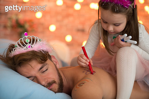 Cute daughter drawing on her sleeping father's back. - gettyimageskorea