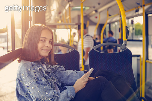 Portrait of smiling girl sitting in bus. Female is using mobile phone while commuting by public transport. She is wearing jacket. - gettyimageskorea