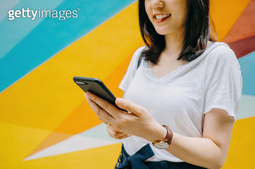 Portrait of smiling young woman using smartphone against colourful background in city - gettyimageskorea