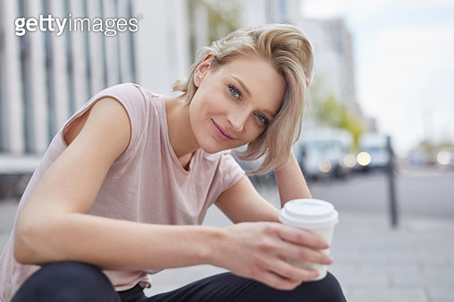 Portrait of smiling blond woman with takeaway coffee in the city - gettyimageskorea