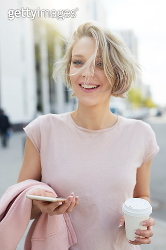 Portrait of happy blond woman with takeaway coffee and cell phone in the city - gettyimageskorea