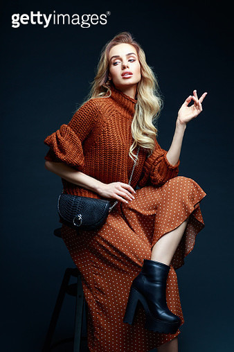 Portrait of long hair blond young woman wearing brown sweater and skirt, holding black purse, sitting on chair, looking away. Studio shot against black background. - gettyimageskorea