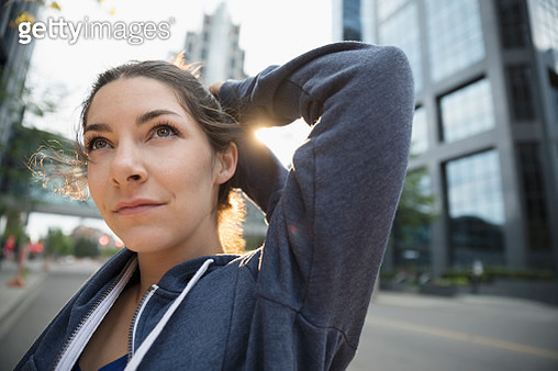 Close up young female runner stretching arm on urban street - gettyimageskorea