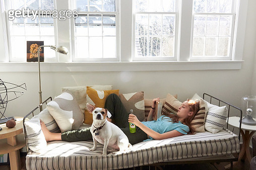 teenage redheaded girl laying on her back on top of indoor bed lounge with dog sitting next to her four windows above her head looking away from the camera knee bend up wearing blue short sleeved shirt and green sweat pants holding green soda small dog - gettyimageskorea