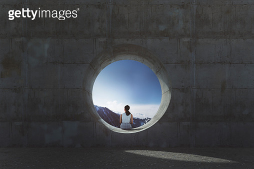 Lonely young woman sitting and looking through concrete window - gettyimageskorea