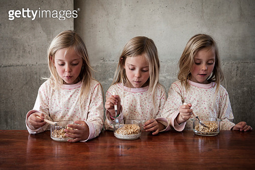 Three girls (7-9) eating cereal - gettyimageskorea