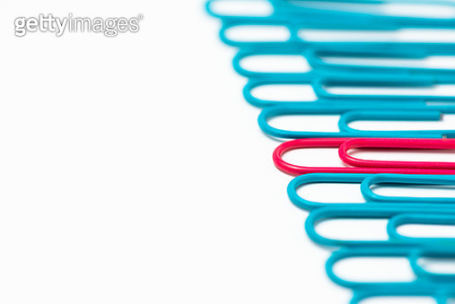 One pink paperclip in a row of blue paperclips on a white background. - gettyimageskorea