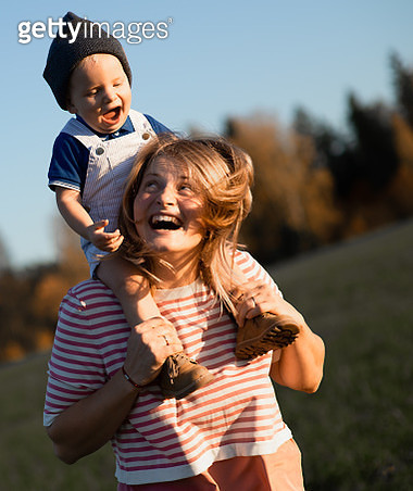 Happy Mother Carrying Son On Shoulders While Standing In Park - gettyimageskorea