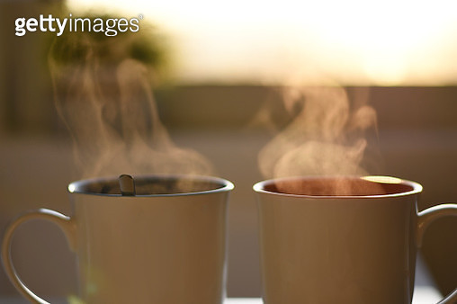 Two cups of hot steaming coffee - gettyimageskorea