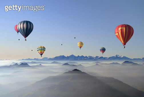 Five colorful hot air balloons flying over layers of mountain ridges partly covered in mist. Morning, sun, Austrian Alps, Groß Glockner, Tyrolia, blue sky.Taken in fall 2011. - gettyimageskorea