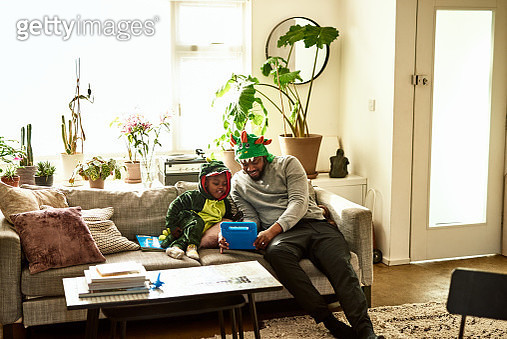 Father and toddler sitting in living room, dressing up, teaching, technology - gettyimageskorea