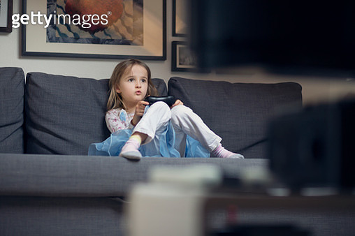 Child playing on a gaming console controller on a sofa - gettyimageskorea