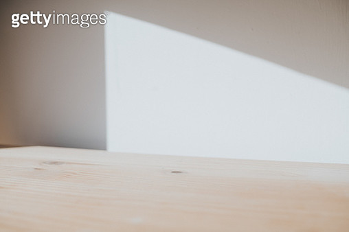 Pocket of light shining on a wall above a table, with shadow. Conceptual with space for copy. Background image. - gettyimageskorea