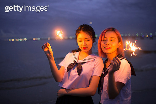 Abstract blur sparklers for celebration background,woman hand holding a burning sparkler light with purple sky background. - gettyimageskorea