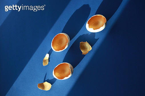 White and golden shells of Easter Eggs over dark blue background in hard light with shadows. Greeting card for holidays. - gettyimageskorea