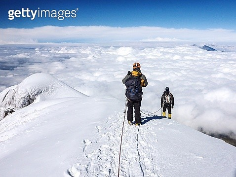 Mountain Climber Walking On Snow Covered Mountain - gettyimageskorea