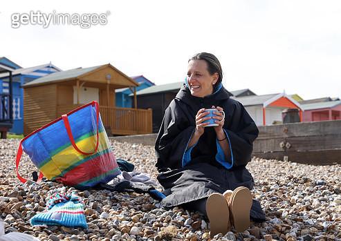 Woman keeping warm on the beach - gettyimageskorea