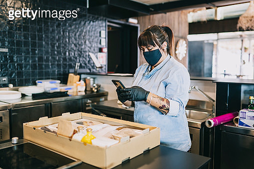 Female chef using smart phone while standing by take out food box at kitchen counter in restaurant during coronavirus - gettyimageskorea