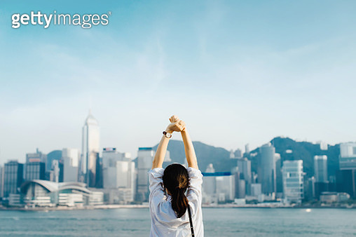 Rear view of woman traveller enjoying her time in Hong Kong, taking a deep breath with hands raised against Victoria Harbour and city skyline - gettyimageskorea