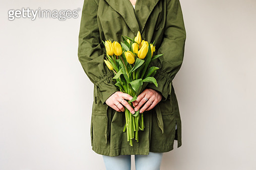 woman with a green coat holding a bunch of yellow tulips in spring - gettyimageskorea