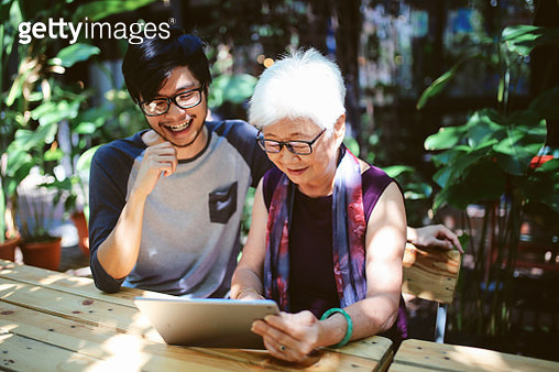 Senior woman looking at the digital tablet, receiving instructions from grandson - gettyimageskorea